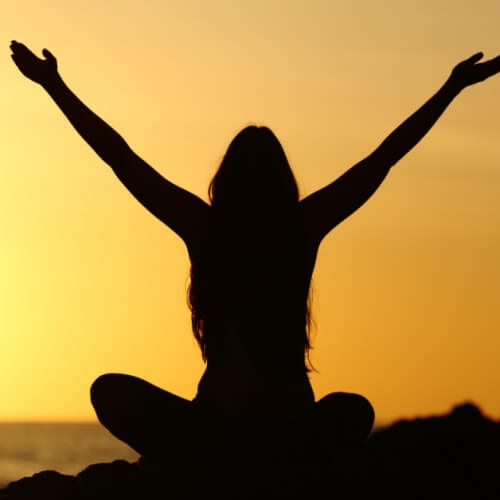 Woman with raised arms watching a sunrise