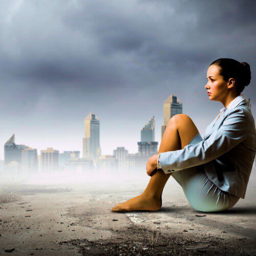 Woman sitting in front of a desolate landscape, licensed through Stock Photo Secrets