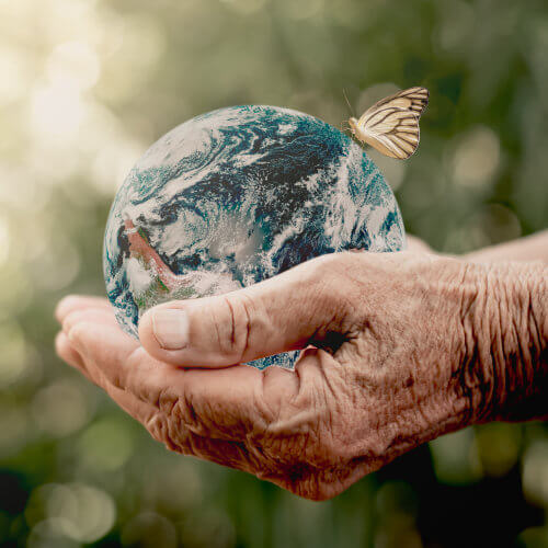 Old woman's hands holding the world