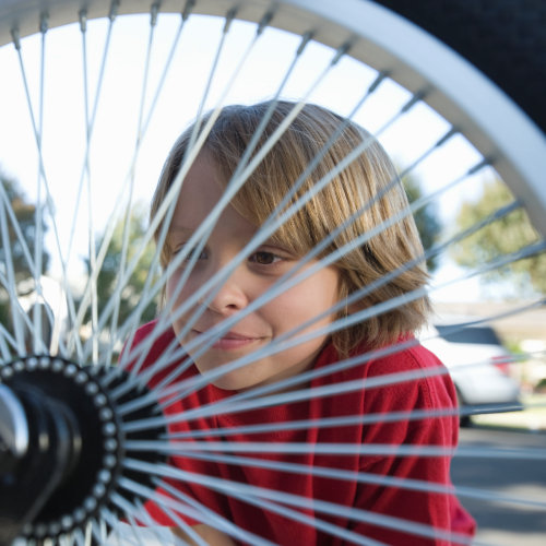 Little child looking through the spokes of a bicycle wheel