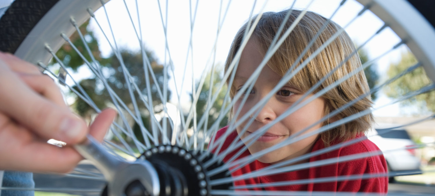 Young child looking through the spokes of a bicycle wheel
