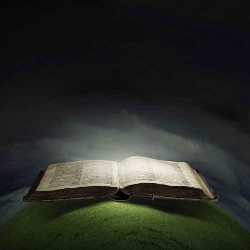 Opened Bible with light on pages on black background