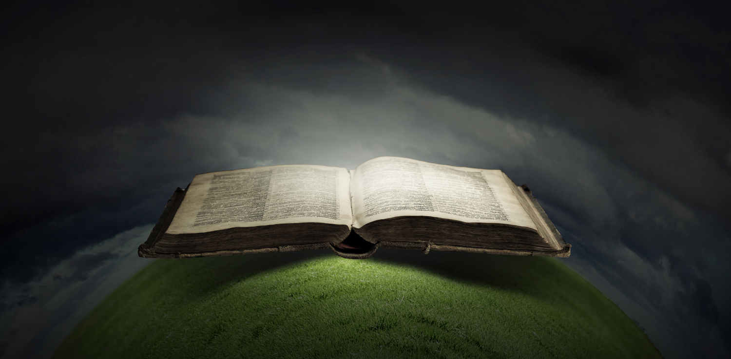 Bible on round grassy ball with light shining down