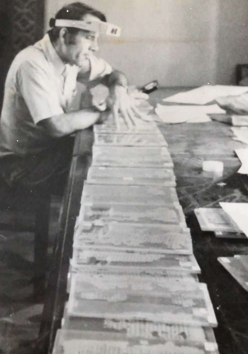 Black and white photo of Charles Hedrick with the Nag Hammadi manuscripts in the 1970s