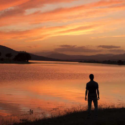 Man on the lake shore contemplates an amazing sunset used to illustrate reading Nag Hammadi texts