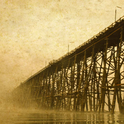 Sepia toned photo of a long, tall wooden bridge over a misty body of water
